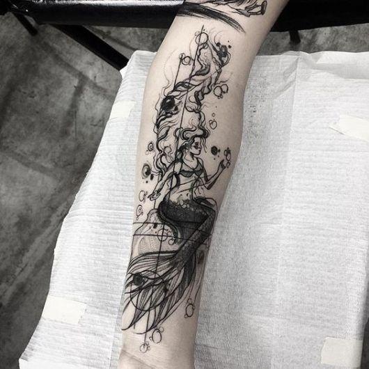 Tatuagem de uma sereia sentada em uma rocha feita em preto e branco no braço