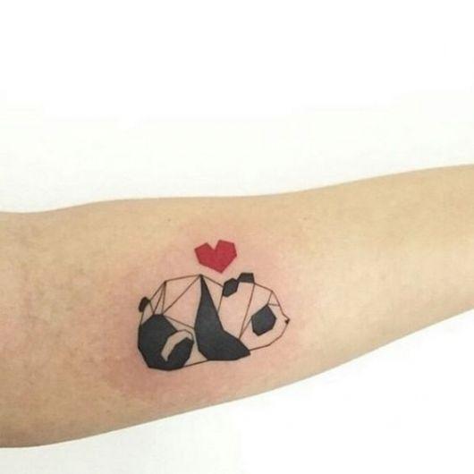 Tatuagem de um urso panda feito de formas geométricas com um coração vermelho acima dele