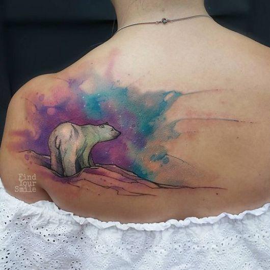 Tatuagem de um urso polar olhando para o horizonte com uma aquarela no céu