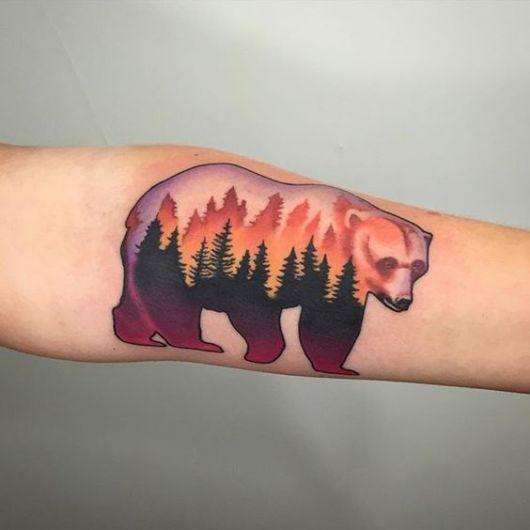 Tatuagem de um urso pardo caminhando. Seu interior é pintado com cores vivas e sombras de árvores desenhadas.