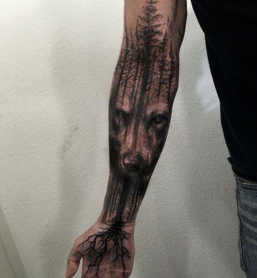 Tatuagem na parte interna do braço do rosto de um urso em meio a uma floreta
