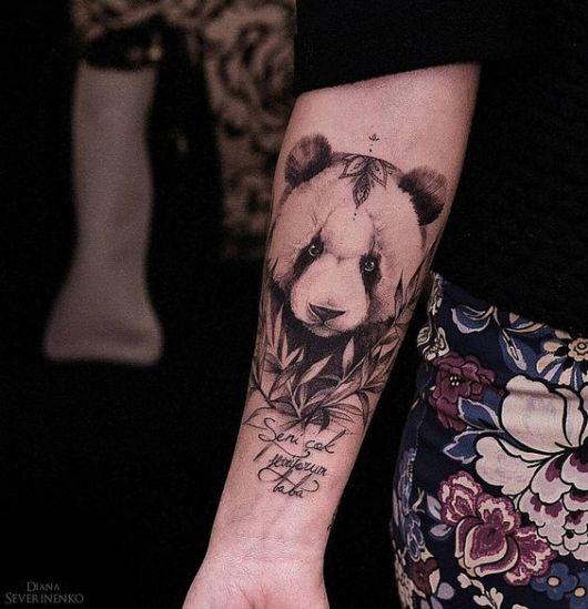 Tatuagem realista de um urso panda olhando para um ponto fixo em meio a dois galhos de bambu