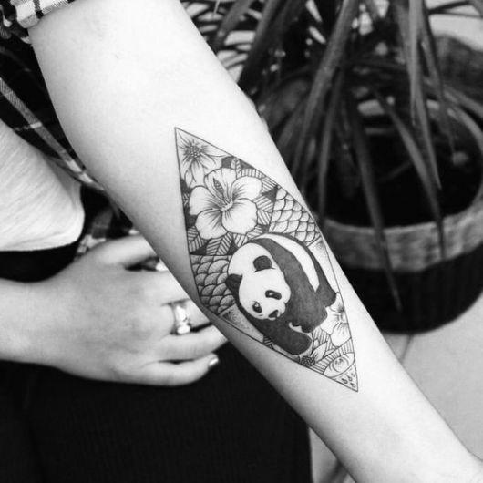 Tatuagem com o contorno de um losango onde dentro pode ser visto um urso panda caminhando