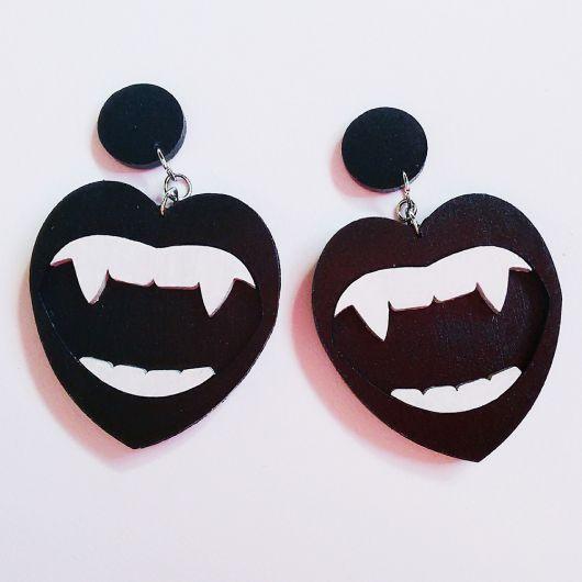 Modelo de brinco em formato de boca, na cor preta com dentes de vampiro, na cor preta.