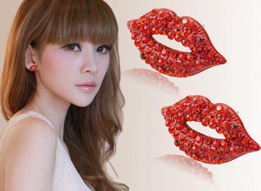 Modelo com brinco em formato de boca na cor vermelha com pedrinhas.