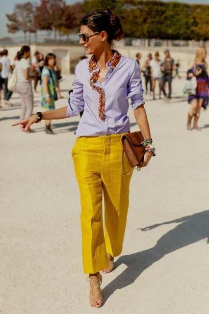 Modelo usa camisa lisa lilás, calça amarela, bolsa e sapato.