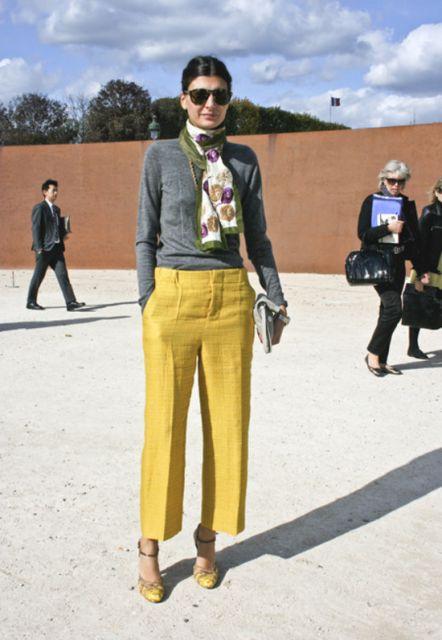 Modelo usa calça amarela queimado, blusa cinza, cachecol estampado e sapato amarelo.