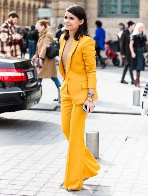 Modelo usa look com calça marela, blazer amarelo e sapato de salto.