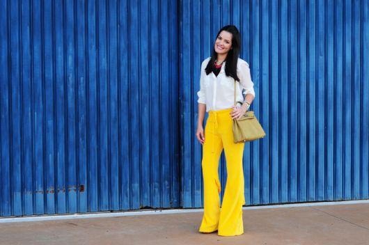 Modelo usa calça amarela, camisa branca e bolsa amarela.