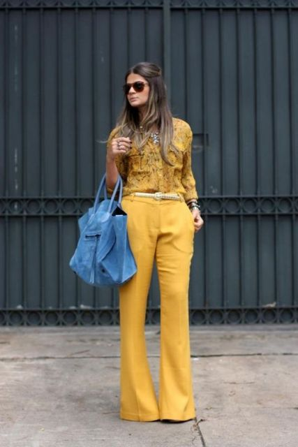 Modelo usa camisa amarela, calça na mesma cor e bolsa azul royal.