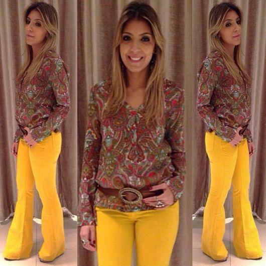 Modelo usa calça flare amarela e blusa estampada.