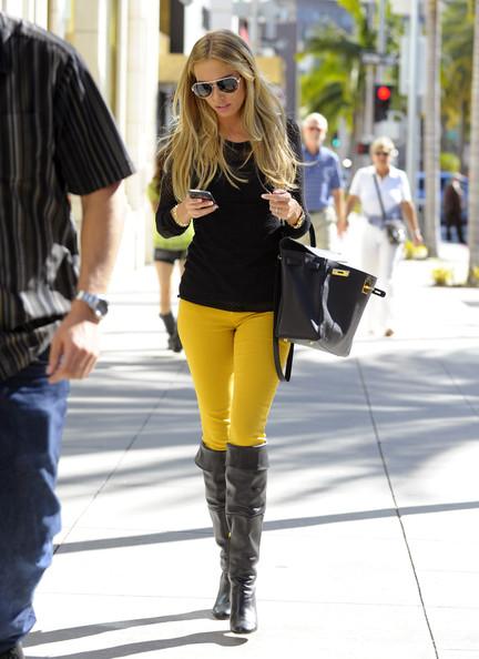 Modelo usa calça amarela, bolsa preta, bota e blusa na mesma cor.