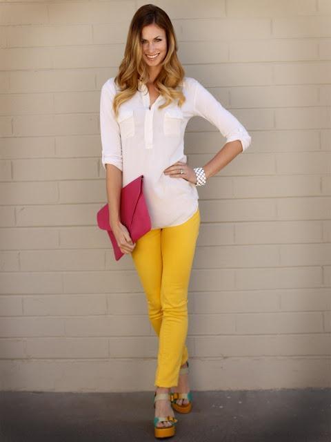 Modelo usa calça amarela, bolsa rosa, camisa branca e sandalia.