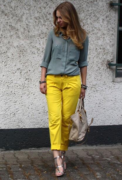Modelo usa calça amarela, camisa cinza, bolsa bege e sandalia prata.