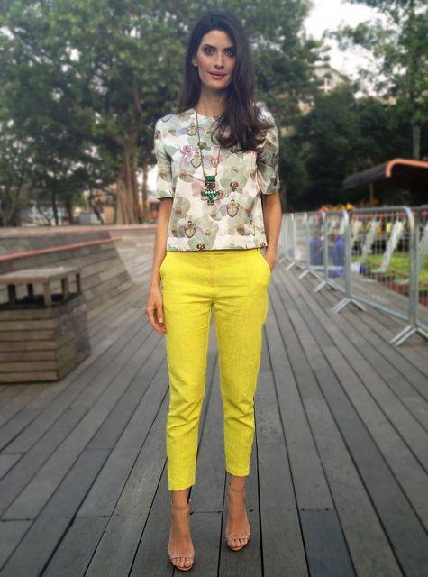Modelo usa calça amarela, sandalia nude e camisa com estampa bege e verde claro.