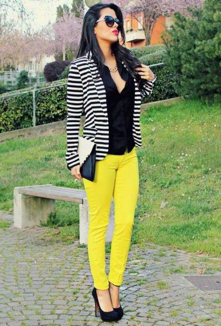 Modelo usa calça amarela, casaquinho listrado de preto e branco, sapato preto e bolsa de mao preta e branca.