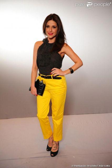 Modelo usa calça amarela, sapato, blusa e sapato preto.