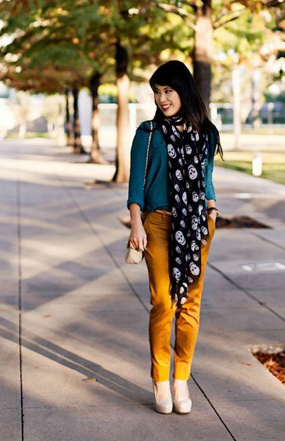 Modelo usa calça amarelo queimado com cachecol estampado em preto e branco, blusinha verde e sapato nude.