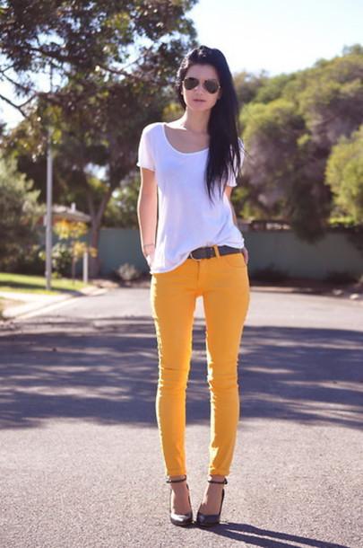 Modelo usa calça amarela com cinto, sapato e camisetinha branca.