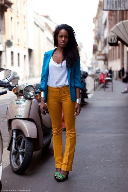 Modelo usa calça amarela com blusa branca, sandalia e casaquinho azul.