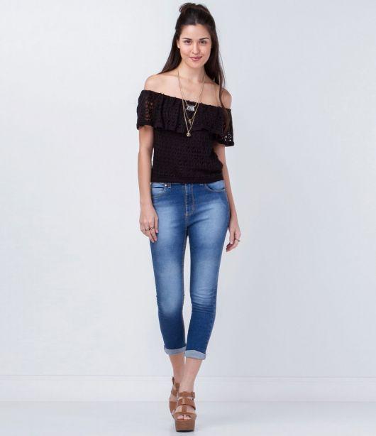 Modelo usa calça jeans azul, blusa preta e sandalia caramelo.