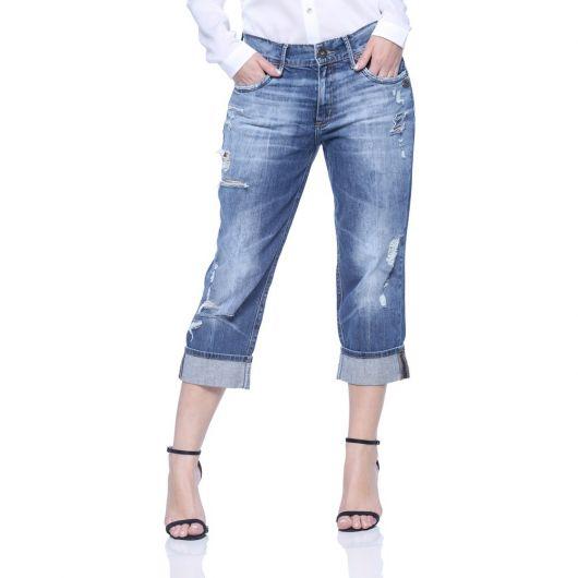 Modelo usa calça jeans azul com detalhes claros, camisa branca e sandalia preta.