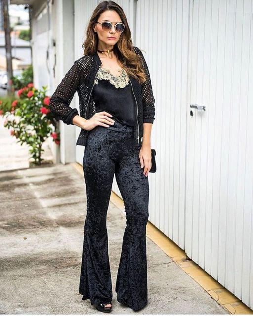 Modelo usa calça flare de veludo preta, blusa preta de alcinha com detalhe de renda branca no busto e casaquinho preto com bolsa de ombro preta.