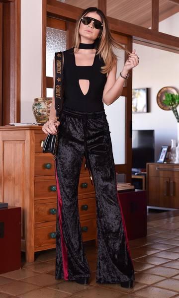 Modelo usa calça preta com detalhe vermelho na lateral, blusinha top preta e bolsa de ombro na mesma cor.