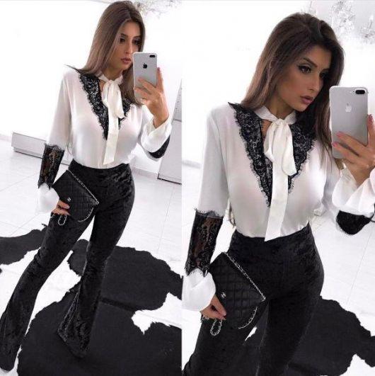 Modelo usa calça flare preta, camisa branca com renda preta e bolsa de mão preta.