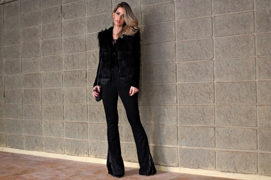 Modelo usa calça preta flare de veludo, bolsa preta e colete preto de pelinhos.