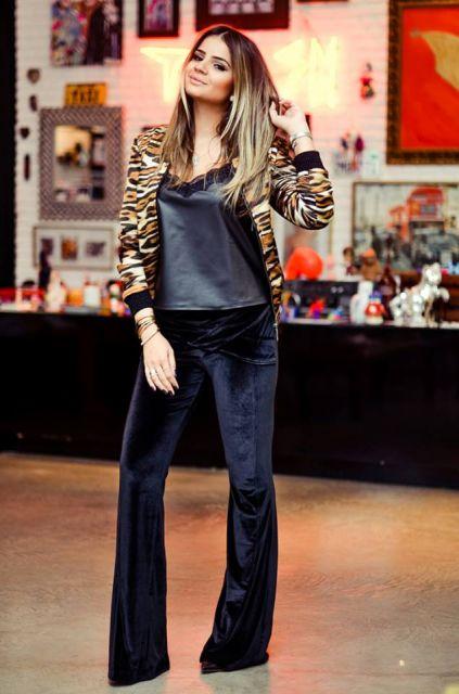 Modelo usa calça preta de veludo, blusa preta de cetim, blazer animal print.