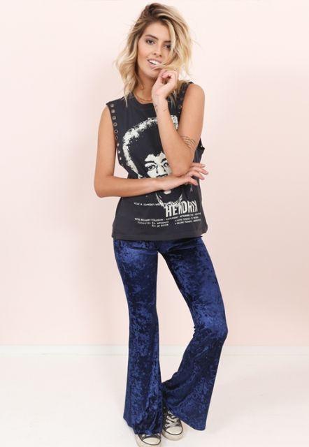 Modelo usa camiseta estampada preta e branco, calça flare azul de veludo com tênis all star.