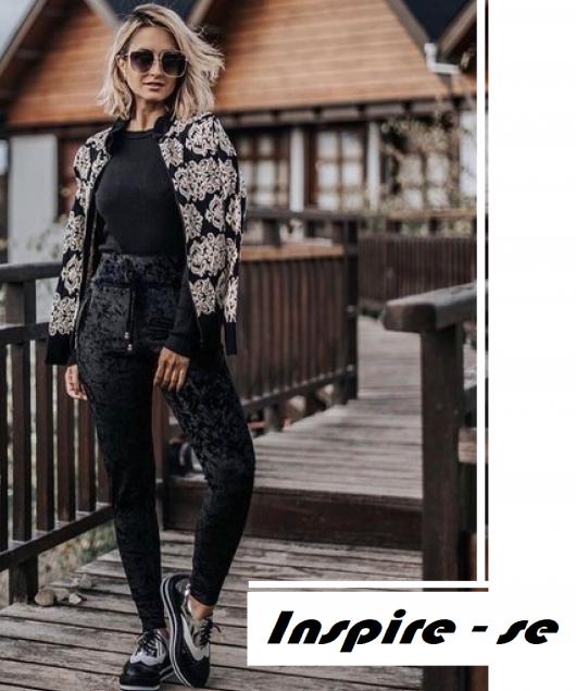 modelo usa calça de veludo preta, blusa na mesma cor, sapato preto baixinho e casaco estampado em cinza em preto.