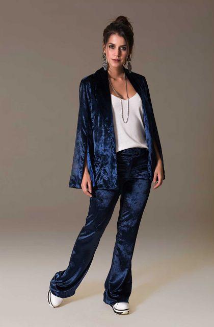 Modelo usa calça e blazer de veludo azul escuro, blusinha branca e tênis.