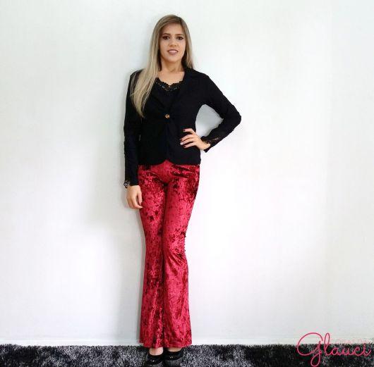 Modelo usa blusa preta, calça vermelha de veludo e sapatilha preta.