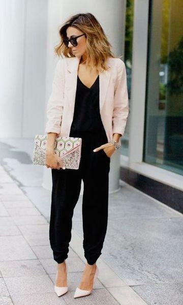 Modelo usa calça e blusa preta com blazer rosê, sapato e bolsa no mesmo tom.