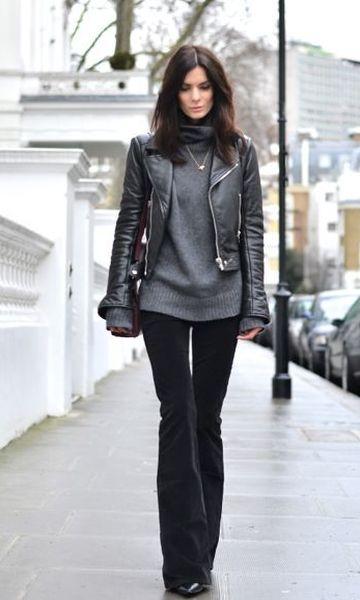 Modelo usa calça flare preta, blusa cinza e jaqueta preta de couro.