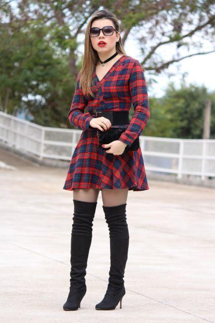 Modelo usa bota de cano longo preta, vestido xadrez vermelho e preto com meia transparente.