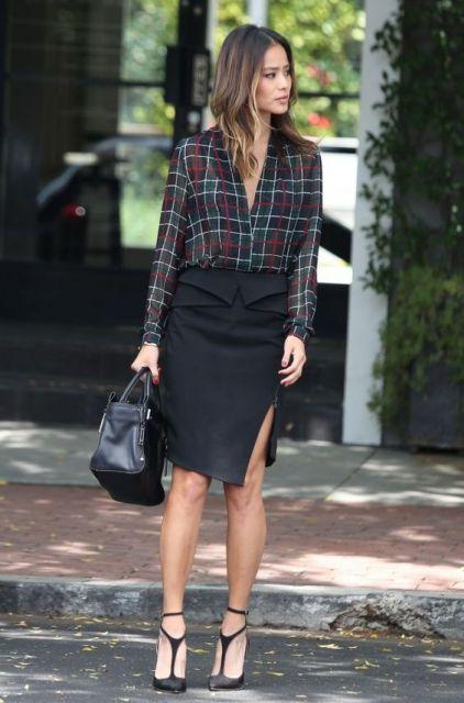 Modelo usa camisa xadrez preta com vermelho e branco, saia midi preta e sapato scarpin preto.
