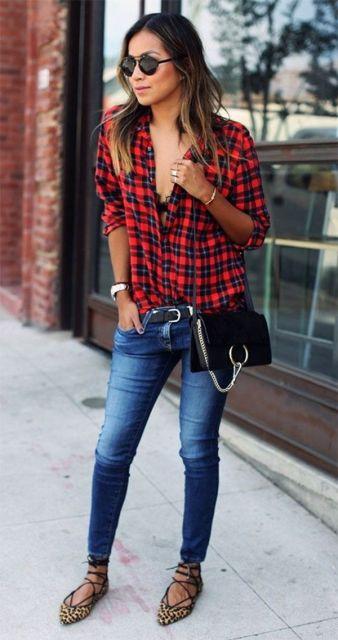 Modelo usa calça jeans azul desbotada com camisa vermelha e preta (xadrez) e sapatilha de amarrações.
