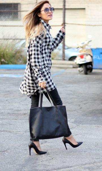 Modelo usa calça preta, scarpin preto bolsa e camisa preta e branca.