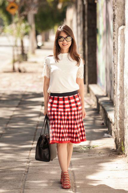 Modelo usa blusa branca, saia vermelha com branco, bolsa preta e sandalinha caramelo.