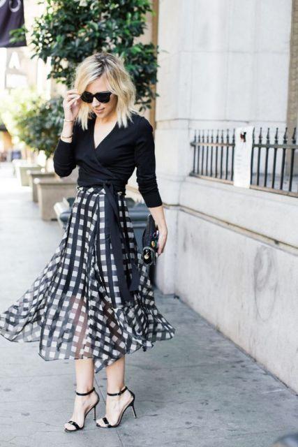 Modelo usa blusa preta saia midi rodada preta e branco e sandalia preta.