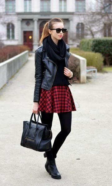 Modelo usa meia calça preta, saia xadrez vermelha, blusa preta, cachecol e botinha.