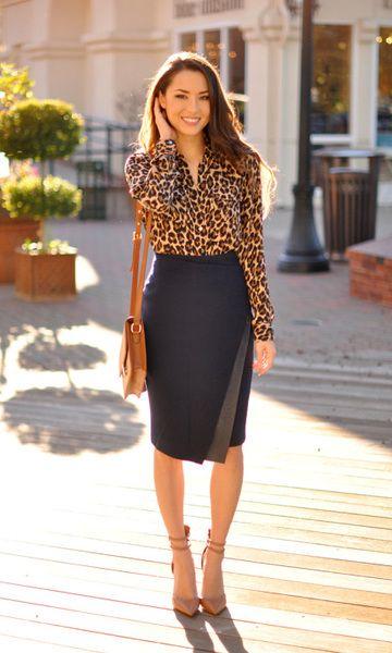 Modelo usa saia preta comprimento ate o joelho, camisa manga longa estampa de onça, bolsa caramelo e sandalia nude.