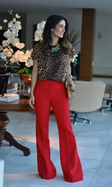Modelo usa calça vermelha pantalona, blusa de mangas curtas estampa de onça e bolsa bege.