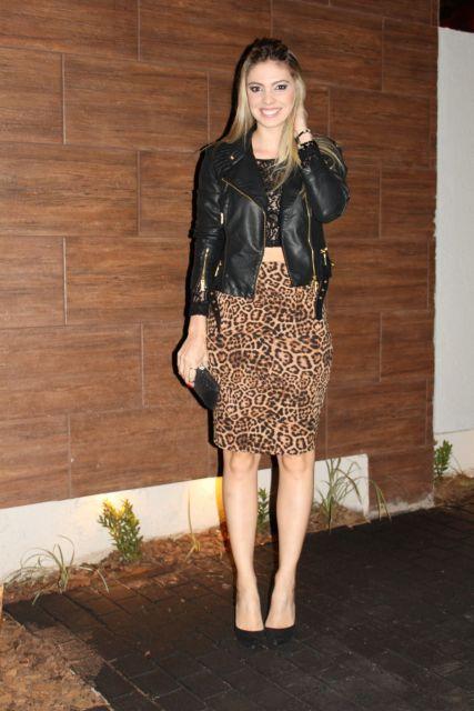 Modelo usa saia de onça, jaqueta de couro, blusa e sapato preto.