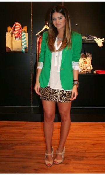 Modelo usa blusa branca, saia estampada de oncinha e blazer verde com sapato nude.