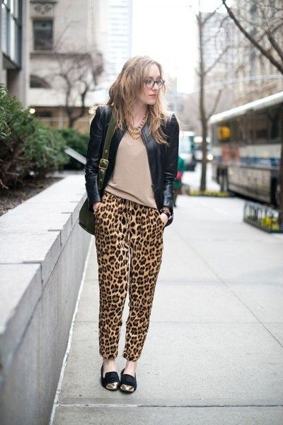 Modelo usa calça estampa de oncinha, blusa nude, jaqueta de couro e sapato preto.