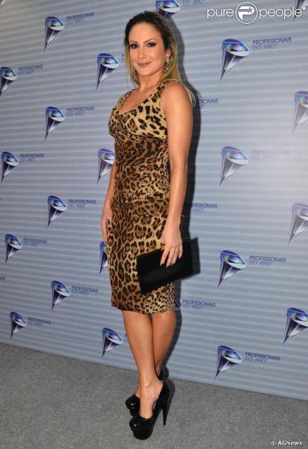 Modelo usa vestido com estampa de onça, amarelo com preto, sapato de salto e bolsa preta.